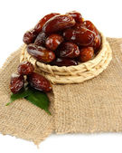 Dried dates on wicker stand sackcloth isolated on white — Stock Photo