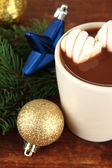 Cup of hot cacao with Christmas decorations on wooden background — Stock Photo