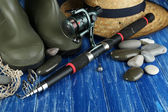 Fishing rod, gumboots and hat on table — Stock Photo
