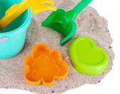 Children's toys on sand isolated on white — Photo