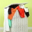 Full laundry basket  on wooden floor on green wall background — Stock fotografie