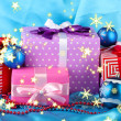 Colorful gifts with blue Christmas balls, snowflakes and beads on blue background — Stok fotoğraf