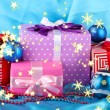Colorful gifts with blue Christmas balls, snowflakes and beads on blue background — Stockfoto