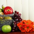 Different fruits in basket and flowers on table — Stock Photo #35845989