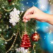 Decorating Christmas tree on bright background — Stock Photo #35846371