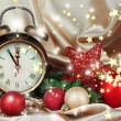 Stock Photo: Alarm clock with Christmas decoration on golden cloth background