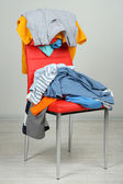 Heap of clothes on color chair — Stock Photo