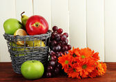 Different fruits in basket and flowers on table — Stock Photo