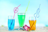 Glasses of cocktails on sand, on bright background — Stock Photo