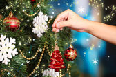 Decorating Christmas tree on bright background — Zdjęcie stockowe