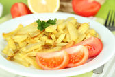 Ruddy fried potatoes on plate on wooden table close-up — Стоковое фото
