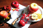Composition with apples and candle on napkin on wooden background — Stock Photo