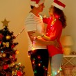 Happy young couple near Christmas tree at home — Stock Photo #35851465