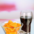 Chips in bowl, cola and TV remote on bright background — Stock Photo