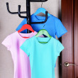 T-shirts hanging on hanger near door — ストック写真