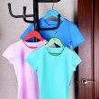 T-shirts hanging on hanger near door — Stok fotoğraf