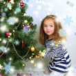 Little girl decorating Christmas tree with baubles in room — Foto de Stock