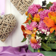 Stock Photo: Flowers composition in crate with decorative hearts on table on wooden background