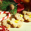 Cookies on ribbons with Christmas decorations on wooden table — Stock Photo #35858345
