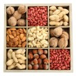 Assortment of tasty nuts in wooden box, isolated on white — Stock Photo #35858895