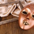 Mask on golden fabric on wooden background — Stock Photo #35859717