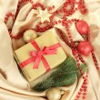 Beautiful bright gift and christmas decor, on silk cloth — Stock Photo