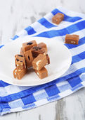 Many toffee on plate on napkin on wooden table — Stock Photo