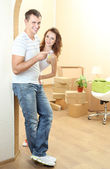 Young couple with keys to your new home on room background — ストック写真