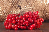 Red berries of viburnum on table on brown background — 图库照片