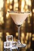 Baileys liqueur in glass on golden background — Stock Photo