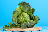 Fresh savoy cabbage on wooden table on blue background — Stock Photo