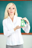 School teacher near blackboard with clock in classroom — Stock Photo