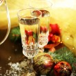 Composition with Christmas decorations and two champagne glasses, on bright background — Stock Photo #35946069
