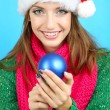 Beautiful smiling girl with Christmas ball on blue background — Stock Photo #35946219