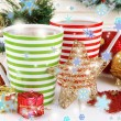 Cups of hot cacao with Christmas decorations on table on wooden background — Stock Photo