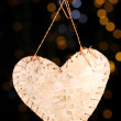 Decorative heart on rope on shiny background — Stock Photo