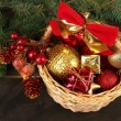 Christmas decorations in basket and spruce branches on wooden background — Stock Photo #35946607