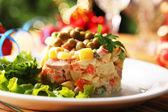 Ensaladilla tradicional olivier, servilleta de color, en mesa de madera, sobre fondo brillante — Foto de Stock