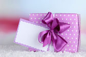 Gift box with blank label on carpet on bright background — Stok fotoğraf
