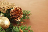 Beautiful Christmas decorations on fir tree on brown background — Stock Photo