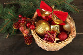 Christmas decorations in basket and spruce branches on wooden background — Stock Photo