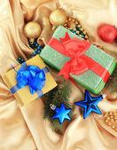 красивые яркие подарки и рождественские декор, на шелковой ткани — Стоковое фото