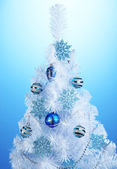 White Christmas tree on blue background — Stock Photo