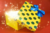 Gift box with bright light on it on red background — Stock Photo
