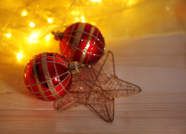Christmas ornaments and garland on wooden table close-up