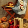 Apples in crate and pumpkins on wooden board and chair on sackcloth background — Stock Photo
