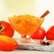 Stock Photo: Ripe persimmons with jam in glass saucer and cinnamon on table on bright background
