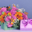 Flowers composition in crate with present on table on grey background — Stock Photo #35996063