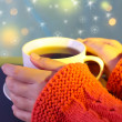 Hands holding mug of hot drink, close-up, on bright background — Stock Photo #35996725