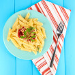Rigatoni pasta dish with tomato sauce on blue wooden table — Stock Photo